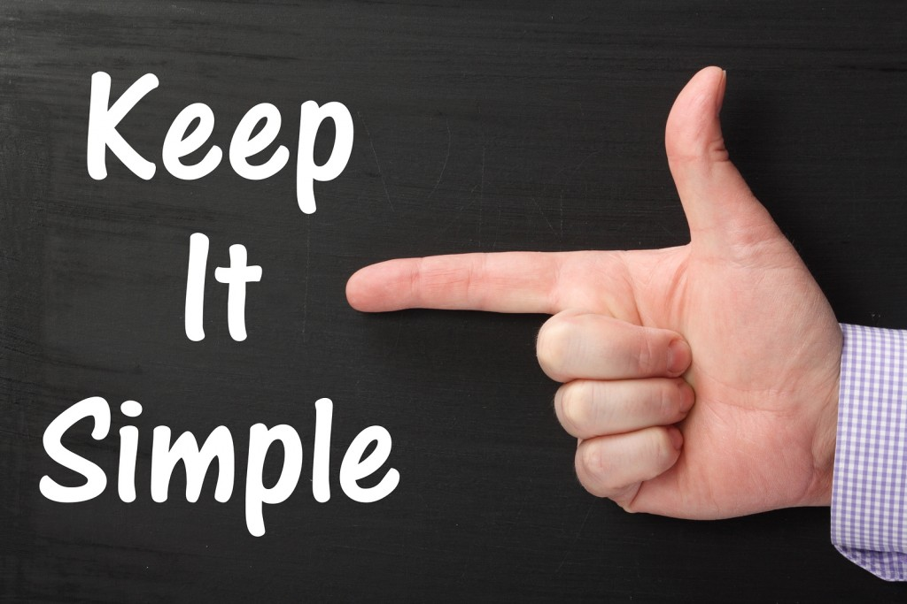 Male hand wearing a business shirt pointing an index finger at the phrase Keep It Simple written on a blackboard